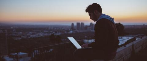 Guy with Laptop sitting on a Roof