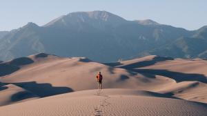 Man walks through desert and leaves footprints.