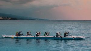 People rowing in front of lilac sky