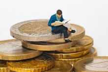 Man sitting on coins reading